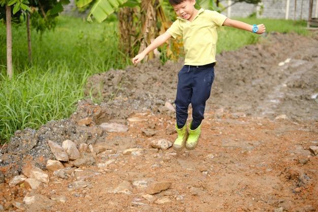 Carino felice piccolo ragazzo asiatico dell'asilo che indossa stivali verdi salta in pozzanghere fangose sulla natura