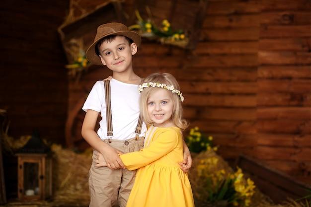 Simpatici bambini felici, un ragazzo e una ragazza nella mangiatoia con gli animali il giorno di pasqua.
