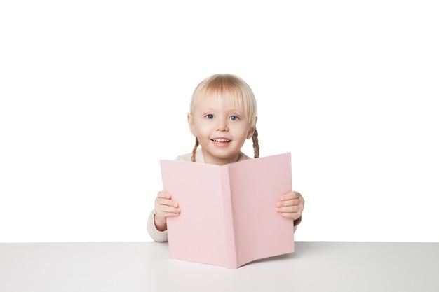 Bambina felice sveglia che legge un libro. isolato su sfondo bianco