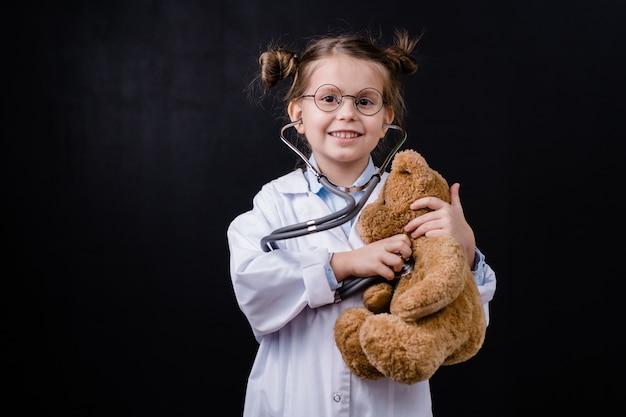 Bambina felice sveglia con lo stetoscopio che esamina teddybear davanti alla macchina fotografica contro lo spazio nero