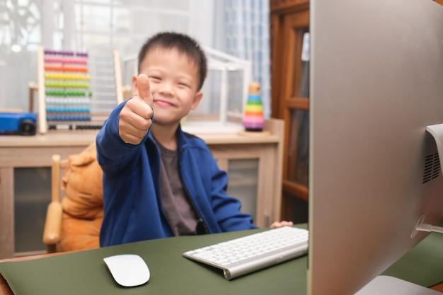 Piccolo bambino asiatico sorridente felice sveglio che mostra i pollici in su mentre utilizza il computer personale a casa, ragazzo dell'asilo che studia in linea, che frequenta la scuola tramite e-learning