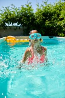 Una bambina carina e felice che gioca in piscina indossando una maschera subacquea blu, si tuffa in acqua, vacanze estive a casa.