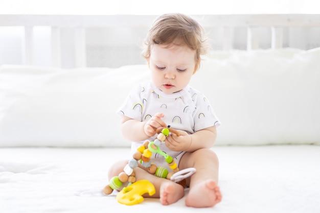 Cute babyt sano è seduto sul letto sulla biancheria da letto sorridente giocando con i giocattoli per i bambini