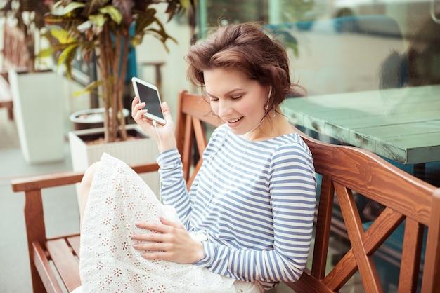 Adolescente caucasico sveglio dei pantaloni a vita bassa con musica d'ascolto delle cuffie e del telefono astuto