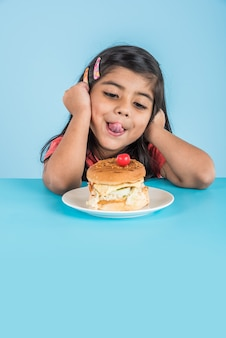 Bambina indiana o asiatica carina che mangia hamburger, sandwich o pizza gustosi in un piatto o in una scatola. in piedi isolato su sfondo blu o giallo.