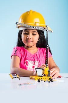 Bambina indiana carina che gioca con una gru giocattolo che indossa un cappello da costruzione giallo o un elmetto, l'infanzia e il concetto di educazione