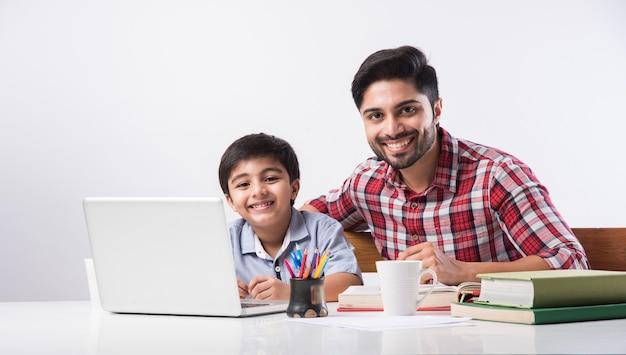 Simpatico ragazzo indiano con padre o tutor maschio che fa i compiti a casa usando laptop e libri - concetto di scuola online online