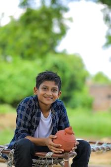 Carino bambino indiano tenendo in mano argilla salvadanaio
