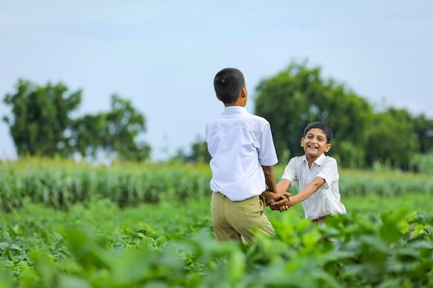 Bambino indiano sveglio che gioca al campo verde