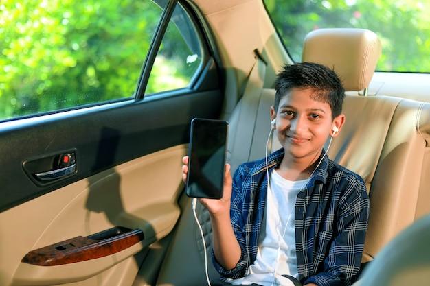 Carino bambino indiano che mostra smart phone con tonfi nel finestrino della macchina