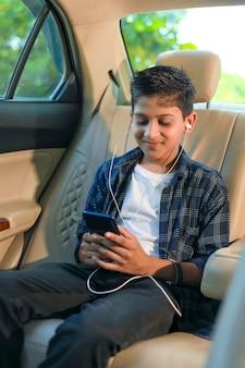 Carino bambino indiano seduto in macchina e utilizzando smart phone e cuffie gadget