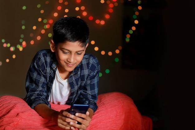 Carino bambino indiano utilizzando smart phone