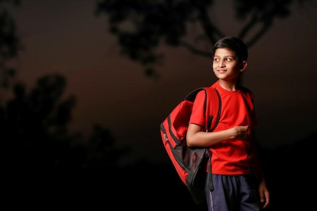 Bambino indiano sveglio con la borsa del sacco sulla strada