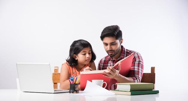 Carina ragazza indiana con padre che studia o fa i compiti a casa usando laptop e libri - concetto di scuola online online