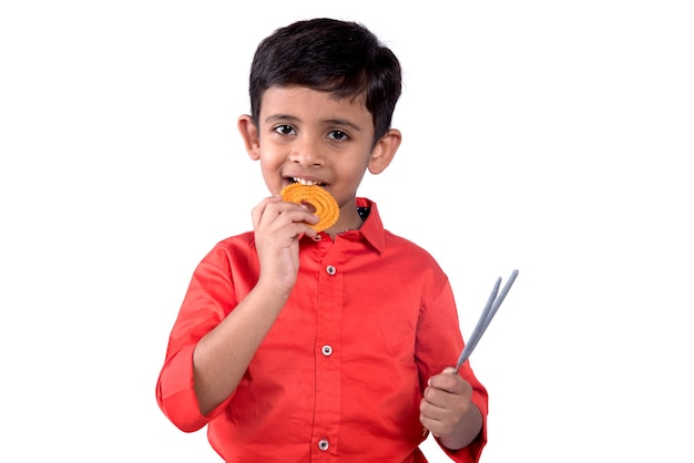 Ragazzo indiano sveglio che mangia murukku o chakli su una parete bianca
