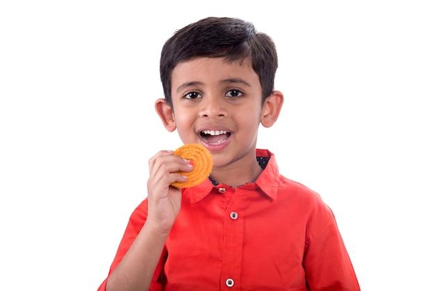 Ragazzo indiano sveglio che mangia murukku o chakli su un bianco