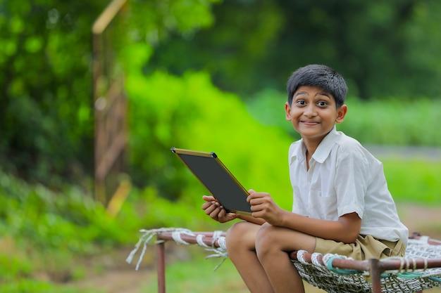Piccolo bambino indiano sveglio che studia a casa