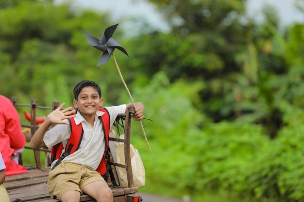 Scolaro indiano sveglio in un carrello di buoi