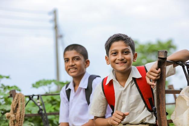 Simpatici scolari indiani in un carrello di buoi