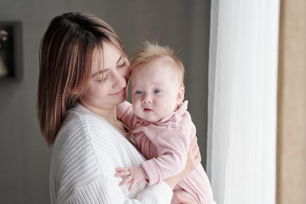 Bambino carino sulle mani della sua giovane madre felice