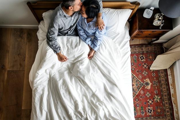 Carino coppia interrazziale sul letto baciando