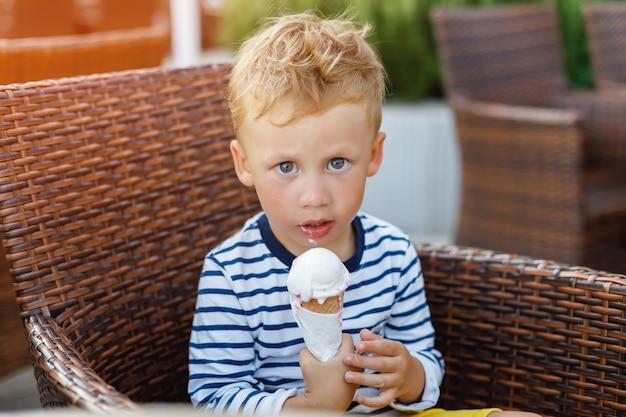 Ragazzo sveglio del bambino che mangia il gelato in caffè