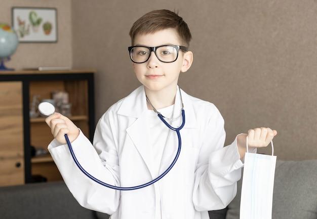 Ragazzo sveglio del bambino indossa l'uniforme medica che gioca medico, ritratto