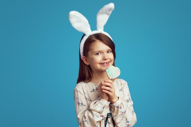 Ragazzo carino con orecchie da coniglio che morde un biscotto a forma di cuore isolato sul muro blu
