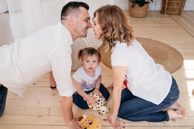 Carina figlia e papà solletico mamma si diverte a giocare insieme a casa, genitori felici e bambina che godono di attività divertenti e comunicazione, famiglia che ride rilassante