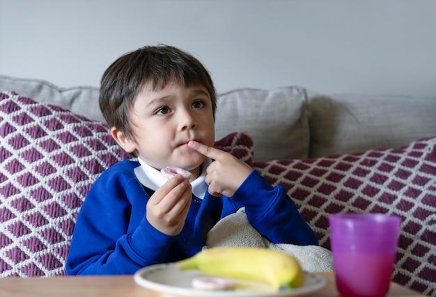 Bambino sveglio che mangia biscotto dell'anello della festa per il suo spuntino dopo la scuola