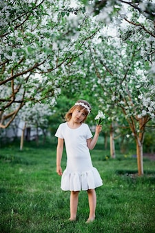 Cute kid girl 5-6 anni tenendo il fiore in piedi nel giardino primaverile in fiore, indossando abiti bianchi e ghirlande floreali all'aperto, la stagione primaverile sta arrivando.