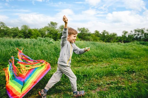 Bambino sveglio che gioca con l'aquilone colorato all'aperto