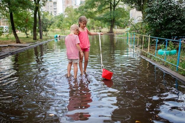 Bambini carini che giocano con la barchetta di carta nelle pozzanghere dopo la calda pioggia estiva felice infanzia