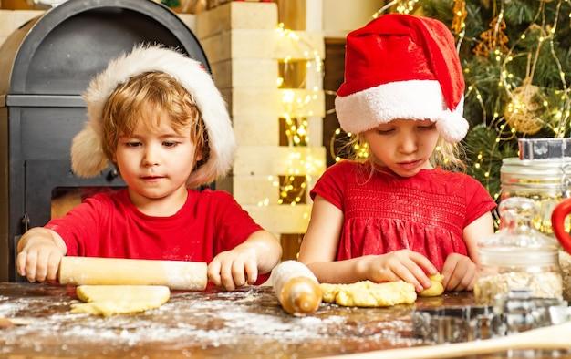 Bambini carini in cappelli di babbo natale che preparano golosità natalizie