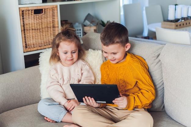 Bambini carini parlano tramite videochiamata utilizzando un tablet. quarantena. una famiglia. casa. accogliente.