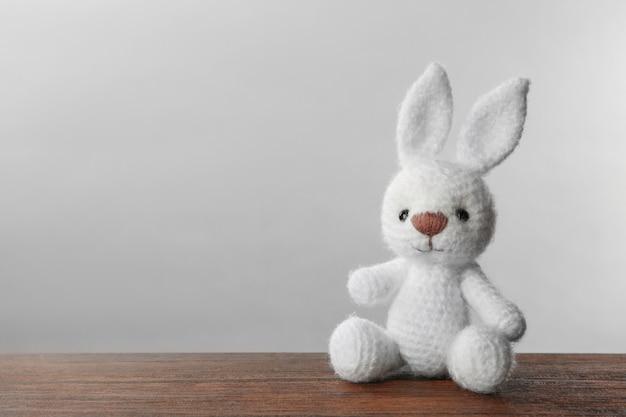 Simpatico coniglietto lavorato a maglia giocattolo sul tavolo su sfondo chiaro