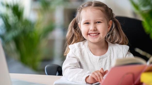Ragazza di risata sveglia che si siede ad una tabella con un libro di testo. concetti di e-learning