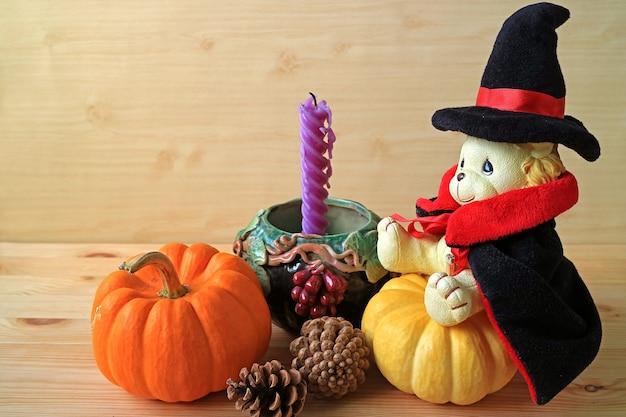 Bambola carina leone in costume da mago che si siede sulla zucca con pigne e candela viola