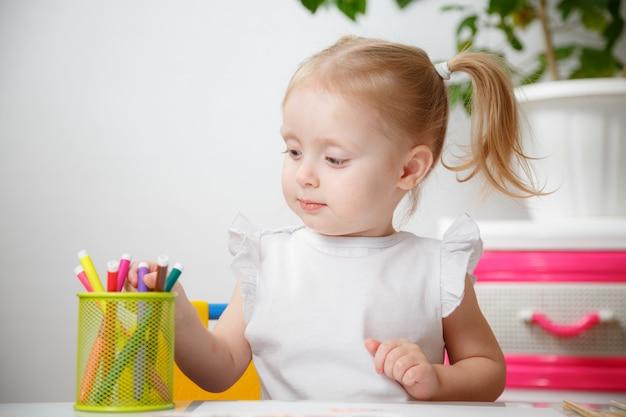 Carina bambina di 3 anni in camicia bianca e code di cavallo disegnare con pennarelli a casa