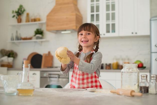 La graziosa bambina di 4 anni con le trecce stende la pasta con un mattarello sul tavolo della cucina.