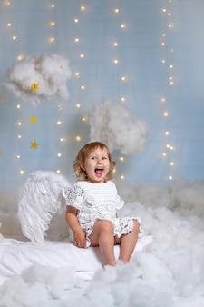 Piccolo angelo sveglio che si siede tra le nuvole che ride allegramente