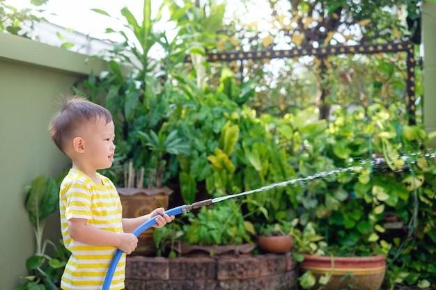 Carino piccolo asiatico 2 anni bambino ragazzo bambino divertirsi innaffiare le piante da tubo flessibile spray nel giardino di casa la mattina di sole, aiutante di casa piccola, faccende per bambini, concetto di sviluppo del bambino