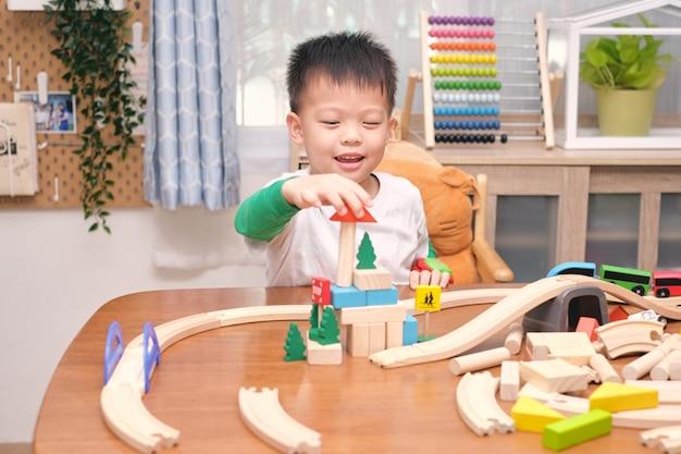 Piccolo bambino asiatico sveglio del ragazzo di 5 anni divertendosi giocando con il treno di legno