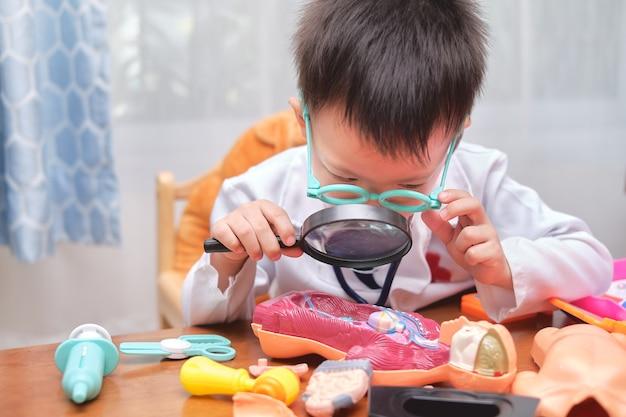 Piccolo ragazzo asiatico sveglio in uniforme del medico che gioca medico a casa, bambino che indossa lo stetoscopio che impara e gioca con il modello di organi del corpo anatomico