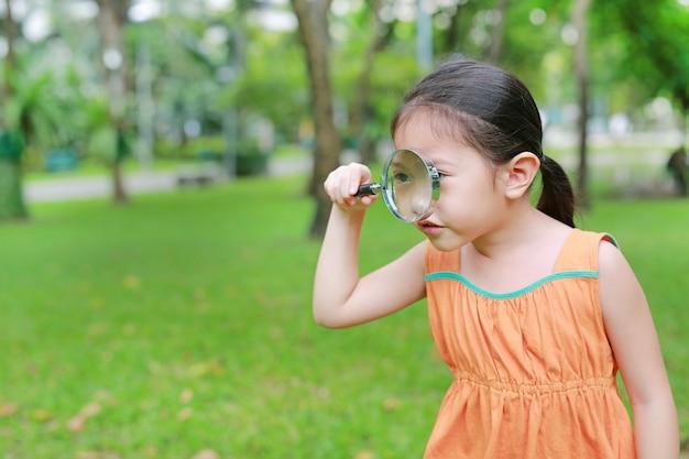 Piccola ragazza sveglia del bambino asiatico che guarda attraverso il vetro di ingrandimento sopra ad erba all'aperto.