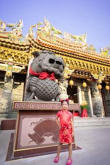 Piccola ragazza asiatica sveglia in vestito tradizionale cinese che sorride e che sta vicino alla statua. felice anno nuovo cinese concetto.