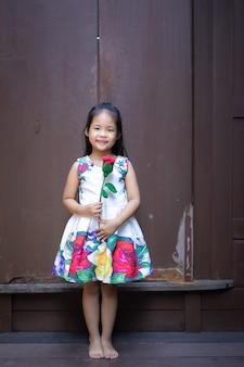 Piccola ragazza asiatica sveglia in vestito che tiene una rosa rossa in casa
