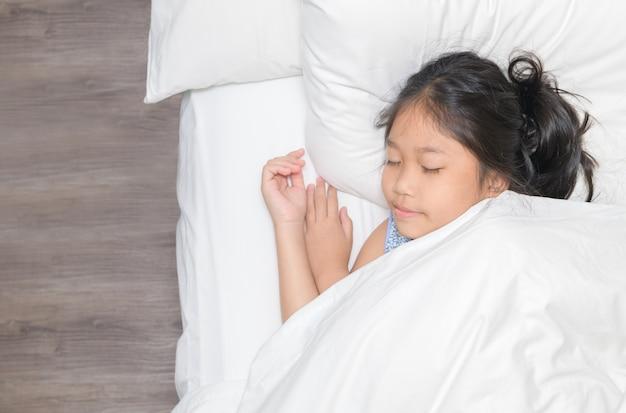 Piccolo sonno asiatico sveglio della ragazza sul letto nella camera da letto.