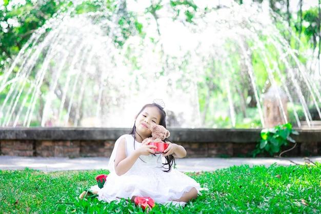 Piccola ragazza asiatica sveglia in vestito bianco che tiene una bambola dell'orso nel parco