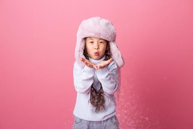 La piccola ragazza asiatica sveglia in vestiti di inverno soffia la neve dalle palme. fine invernale, sfondo rosa, spazio per il testo